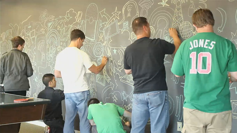 co-workers creating a chalk board art mural at the butchertown office